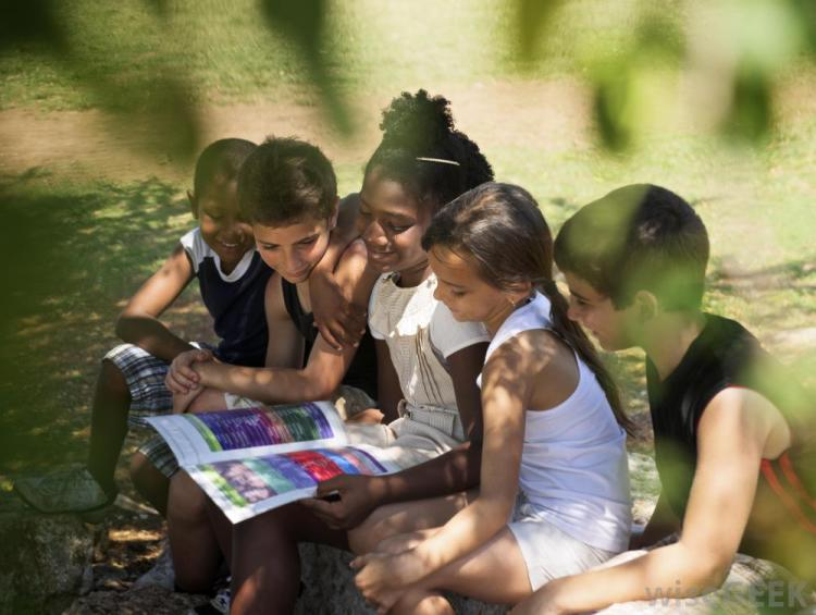 group-of-children-reading-book-near-water